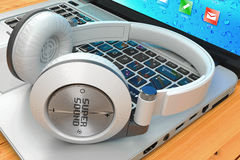 Wireless headphone and laptop on wooden table Stock Images