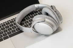 Wireless headphones and laptop computer. On table royalty free stock images