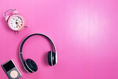 Wireless headphones and media player, pink alarm clock on pink p royalty free stock photo
