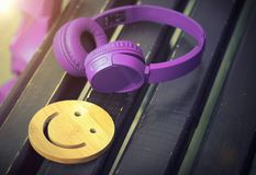 Fine music for perfect mood. Wireless headphones of purple color lie on a dark wooden bench. A wooden smile. The concept of love f stock images