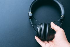 Wireless headphones. Wireless headphone is hold or hanging by a man right hand with black background and copy space for text royalty free stock image
