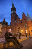 Wireless internet. Man catching wireless internet on his laptop on the city square Royalty Free Stock Photo