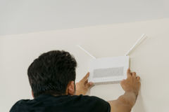 Wireless internet connection technology. The technicians are installing a wireless internet access point connection on the wall of the room Royalty Free Stock Images