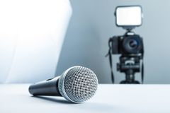 A wireless microphone lying on a studio table against the background of the DSLR camera to led light and softbox stock image
