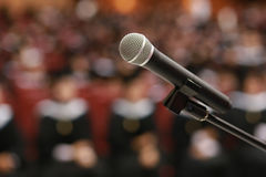 Wireless microphone on stage in auditorium with graduate student Royalty Free Stock Images