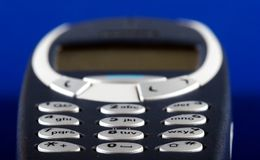 Wireless mobile phone. Close-up of the mobile phone keypad on a blue background Royalty Free Stock Photo