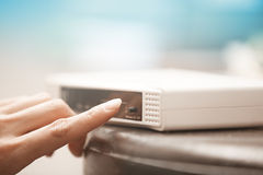 Wireless modem. Human hand turning on wireless modem. Close-up horizontal photo Stock Image