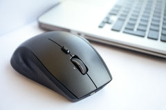Wireless mouse. Is located near the laptop. White background, close up Stock Photos