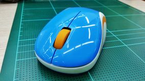 Wireless Mouse. Blue wireless mouse on cutting mat Royalty Free Stock Image