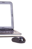 Wireless mouse facing a laptop. royalty free stock image