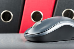 A wireless mouse placed on notebook and three folders in the bac Stock Image
