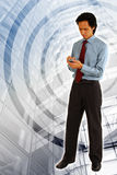Wireless on the Move. Young Asian Business Man / Entrepreneur using the wireless / Wi-Fi connection on his mobile phone/ smartphone. Modern Building background Royalty Free Stock Images