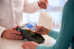 Wireless payment using smartphone and NFC technology. Close up. Customer paying with smart phone in pharmacy. Close Up shopping Royalty Free Stock Photography