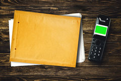 Wireless phone and blank envelope on tabletop Royalty Free Stock Photography