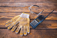 Wireless radio communication,cotton gloves. Safety glasses  on a wooden floor Stock Photos