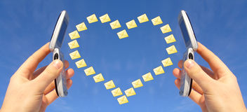 Wireless Romance. Two cellphones held against a blue background with a yellow heart made of small envelopes between them, symbolizing a love or romantic Stock Images