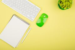 Wireless slim white keyboard and green mouse, notepad, flower on. Yellow background Stock Photo