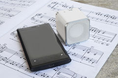 Wireless speaker and cell phone on a musical score.  Stock Photography