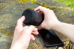 Wireless speaker connected to smartphone in outdoor entertainment. Royalty Free Stock Images