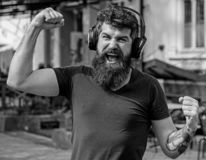 Wireless technologies concept. Hipster with headphones on happy face listening music while walking. Man with long beard stock photos