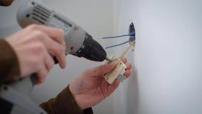 Wireman está conectando los alambres con un mecanismo del mercado eléctrico durante la reparación dentro, usando un vuelta-tornil almacen de video