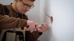 Wireman está pelando los alambres para los zócalos de la instalación, cortando una envoltura de cable, usando el cuchillo de los  almacen de video
