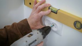 Wireman is mounting a double socket on a white wall inside a flat, aligning and twisting bolts by screwdriver. Wireman is mounting a double socket on a white stock footage