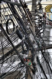 Wires on utility pole. A jumble of electrical and telephone wires attached to a utility pole in Bangkok, Thailand Stock Photos