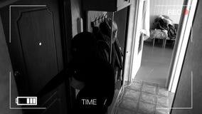 Wirkliche Überwachungskameras fingen und notierten den Einbrecher, der in das Haus einbricht, sahen jemand und Läufe weg stock footage