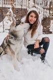 Wirkliche Freundschaft des Überraschens der jungen Frau, die Winterzeit mit heiserem Hund genießt Hübsches reizend Mädchen, das d stockfotos