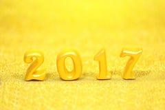 2017 wirkliche Gegenstände 3d auf Goldfunkelnhintergrund, guten Rutsch ins Neue Jahr-Konzept Stockbilder
