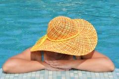 Wirkliche weibliche Schönheit, die im Swimmingpool sich entspannt lizenzfreies stockfoto