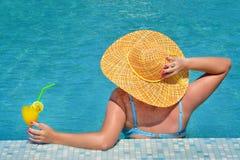 Wirkliche weibliche Schönheit, die im Swimmingpool sich entspannt Stockbilder