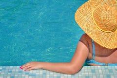 Wirkliche weibliche Schönheit, die im Swimmingpool sich entspannt Stockfoto
