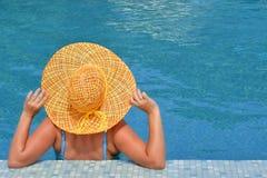 Wirkliche weibliche Schönheit, die im Swimmingpool sich entspannt Stockbild