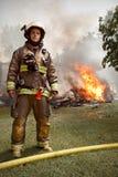 Wirklicher Feuerwehrmann mit Haus auf Feuer im Hintergrund Lizenzfreies Stockfoto