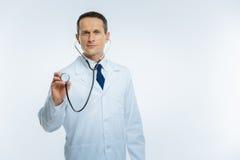Wirklicher medizinischer Fachmann mit Stethoskop hörend auf geduldiges Herz Stockfoto