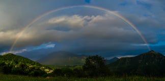 Wirklicher Regenbogen über einem kleinen Dorf Lizenzfreie Stockbilder