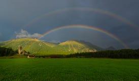 Wirklicher Regenbogen in einer Bergwiese Stockbilder