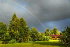 Wirklicher Regenbogen gegen einen stürmischen Himmel Lizenzfreie Stockfotografie