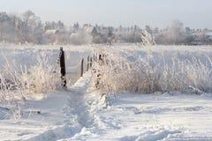 Wirklicher russischer Winter Winter-Landschaft mit Spur über der gefährlichen ländlichen Hängebrücke über dem nebeligen Fluss Sno Lizenzfreie Stockbilder