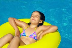 Wirkliches entzückendes Mädchen, das im Swimmingpool sich entspannt Lizenzfreie Stockfotografie