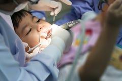 Wirkliches Ereignisfoto, netter kleiner asiatischer Junge, der im zahnmedizinischen ch sitzt Lizenzfreie Stockfotos