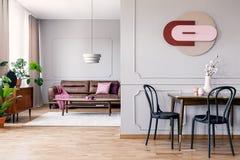 Wirkliches Foto des Wohnzimmerinnenraums des offenen Raumes mit moderner Uhr auf Wand mit Formteil, Tabelle mit schwarzen Stühlen stockfotos
