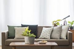 Wirkliches Foto einer Couch mit den Kissen, die hinter einer Tabelle mit stehen stockbilder
