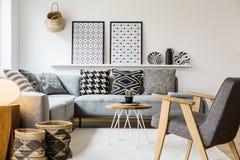 Wirkliches Foto einer kleinen Tabelle, die zwischen einem Sofa mit Kissen steht lizenzfreie stockbilder