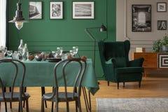 Wirkliches Foto einer Tabelle mit grünem Stoff und schwarzen Stühlen in unscharfem Vordergrund und des bequemen Lehnsessels im Hi lizenzfreie stockbilder