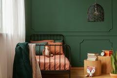 Wirkliches Foto eines netten, gr?nen und orange Schlafzimmerinnenraums f?r ein Kind mit Pl?schfuchsspielwaren, formend auf gr?ner stockbild