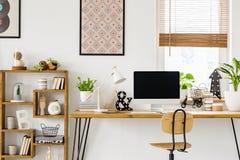 Wirkliches Foto eines Schreibtisches mit einem Bildschirm, einer Lampe und Verzierungen stockfotos