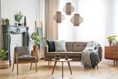Wirkliches Foto eines Sofas mit den Kissen und Decke, die nahe bei a stehen stockfotografie